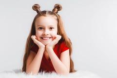 A menina adolescente feliz emocional que veste um t-shirt vermelho e chifres deu forma ao cabelo fotos de stock royalty free
