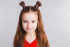 A menina adolescente feliz emocional que veste um t-shirt vermelho e chifres deu forma ao cabelo imagem de stock