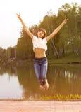 Menina adolescente feliz que salta no bom dia de verão fotos de stock