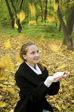 A menina adolescente feliz trava as folhas no parque do outono Fotografia de Stock
