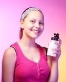 A menina adolescente guarda a garrafa com água e sorriso Fotografia de Stock Royalty Free
