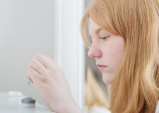 A menina adolescente guarda a lente de olhos azuis imagem de stock royalty free
