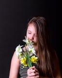 A menina adolescente inala o aroma do ramalhete dos narcisos amarelos Foto de Stock Royalty Free