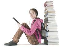 A menina adolescente lê o ebook perto da pilha de livros Foto de Stock Royalty Free