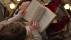 A menina adolescente lê um livro ao sentar-se no assoalho coberto com um tapete quadriculado Natal, luzes, conforto da casa video estoque