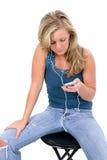 Menina adolescente loura bonita que escuta IPod Fotos de Stock Royalty Free
