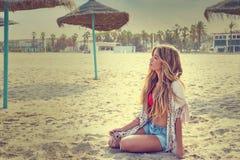 A menina adolescente loura senta-se na areia da praia imagens de stock royalty free