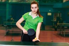 A menina adolescente luz-descascada bonita nos esportes forma guardar uma bola e uma raquete para o tênis de mesa fotos de stock