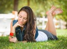 Menina adolescente melancólica da raça misturada que coloca na grama com flor imagens de stock royalty free