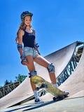 A menina adolescente monta seu skate Fotografia de Stock Royalty Free