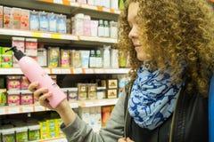 A menina adolescente na loja escolhe a higiene pessoal Imagens de Stock Royalty Free