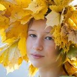 A menina adolescente nas folhas de outono douradas envolve-se fotos de stock royalty free