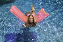 Menina adolescente no biquini cor-de-rosa em um flutuador imagens de stock