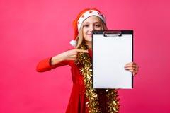 Menina adolescente no chapéu e no ouropel de Santa no pescoço, guardando a tabuleta com c fotos de stock royalty free