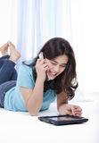 Menina adolescente no computador e no telefone da tabuleta Foto de Stock