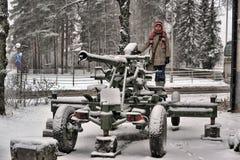 Menina adolescente no inverno perto do canhão velho da segunda guerra mundial Fotografia de Stock
