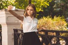 A menina adolescente no parque do outono está tomando o selfie Foto de Stock