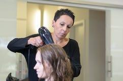 Menina adolescente no salão de beleza que seca seu cabelo com secador do sopro fotografia de stock royalty free