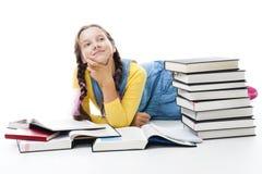 A menina adolescente nova coloca com muitos livros fotos de stock