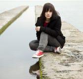 Menina adolescente nova na água próxima ao ar livre imagem de stock royalty free