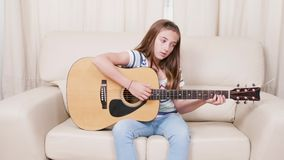 Menina adolescente que aprende jogar a guitarra acústica de seis cordas na sala de visitas