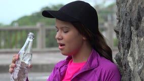 Menina adolescente que bebe a água engarrafada foto de stock