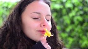 Menina adolescente que cheira a flor amarela video estoque