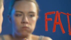 Menina adolescente que come avidamente o bolo, palavra gorda escrita no espelho, desordem da bulimia vídeos de arquivo