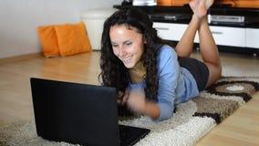 Menina adolescente que encontra-se com tabuleta do portátil video estoque