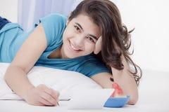 Menina adolescente que encontra-se no assoalho que escreve uma letra ou uma nota Fotos de Stock Royalty Free