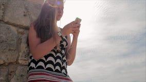 Menina adolescente que escuta a música com os fones de ouvido no smartphone em um fundo do mar e nas ruínas da cidade antiga video estoque