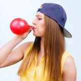 Menina adolescente que funde o balão vermelho Foto de Stock