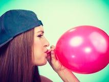 Menina adolescente que funde o balão vermelho Imagens de Stock
