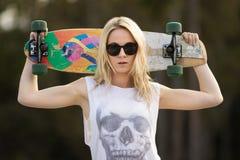 Menina adolescente que guarda o skate Foto de Stock