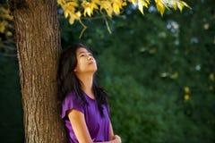 Menina adolescente que inclina-se contra a árvore com as folhas de outono que olham acima Fotografia de Stock