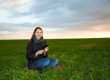 Menina adolescente que lê o livro eletrônico ao ar livre Fotografia de Stock Royalty Free