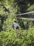 Menina adolescente que monta um zipline com a opinião da floresta de atrás fotos de stock royalty free