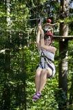 Menina adolescente que monta um Zipline na floresta imagens de stock royalty free