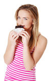 Menina adolescente que morde uma barra de chocolate. Fotografia de Stock Royalty Free