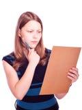 Menina adolescente que olha o papel Imagens de Stock Royalty Free
