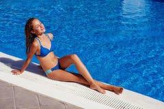 Menina adolescente que relaxa perto da piscina Fotografia de Stock Royalty Free
