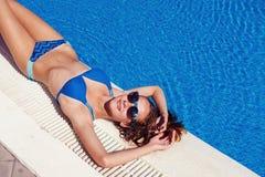 Menina adolescente que relaxa perto da piscina Fotografia de Stock