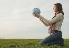 Menina adolescente que senta-se com um globo foto de stock royalty free