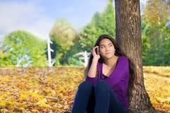 Menina adolescente que senta-se contra a árvore do outono usando o telefone celular Fotografia de Stock Royalty Free