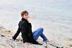 Menina adolescente que senta-se no seixo Imagens de Stock