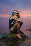 Menina adolescente que senta-se no tiro de pedra da forma no por do sol Imagens de Stock Royalty Free