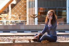 menina adolescente que tem uma conversa do telefone celular em uma metrópole fotos de stock