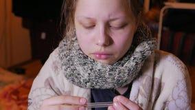 Menina adolescente que tem uma gripe ou um frio Usando o termômetro, 4K UHD video estoque