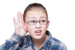 A menina adolescente que tenta ouvir-se faz um gesto à mão, foto de stock