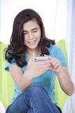 Menina adolescente que texting em um telefone de pilha Fotografia de Stock